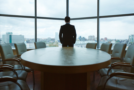 executive chair: Back view of businessman looking through office window