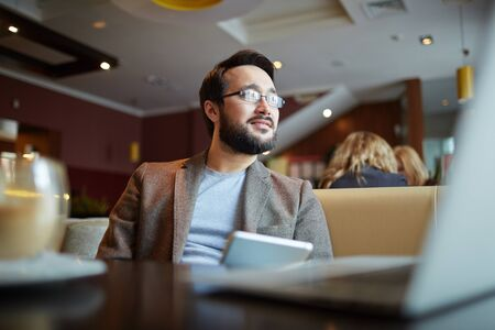 work addicted: Pensive businessman with touchpad relaxing in cafe