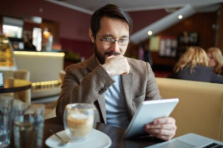 touchpad: Young businessman using touchpad while sitting in cafe Stock Photo