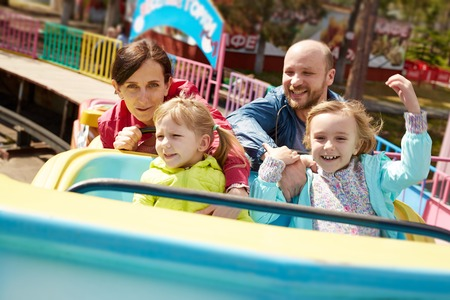 family in park: Family of four having fun in amusement park Stock Photo