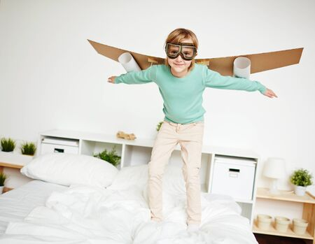 selfmade: Cute girl with self-made carton airplane behind back looking at camera Stock Photo
