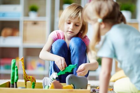 zoo youth: Cute girls playing with toy animals in kindergarten Stock Photo