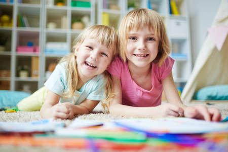 Happy girls looking at camera in kindergarten
