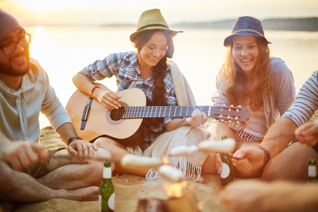 among: Cheerful girls singing by campfire among friends