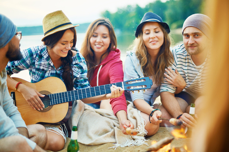 Group of young campers with drinks and guitar spending evening by campfire photo