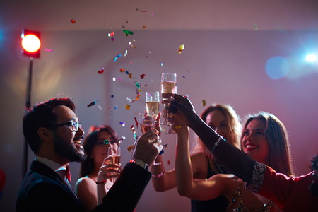 clinking: Cheerful young friends toasting with flutes of champagne