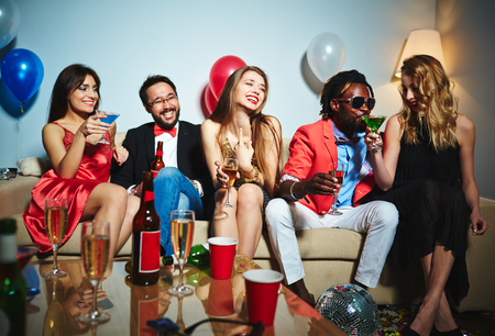 clubber: Relaxed girls and guys with drinks sitting on sofa Stock Photo