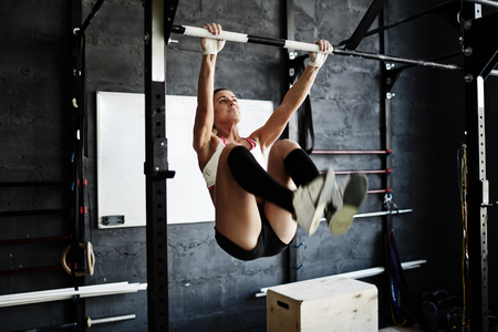 pullups: Strong sporty woman doing pull-ups in gym Stock Photo