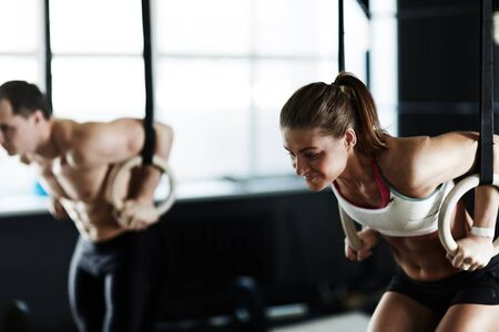 brawny: Sporty man and woman training on sports rings in gym Stock Photo