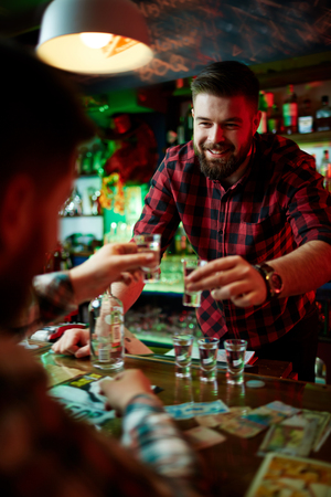 over the counter: Happy barman and guy toasting with vodka over bar counter Stock Photo