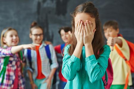 desolaci�n: Colegiala ocultando su rostro en las palmas en el fondo de los compa�eros de clase burlas