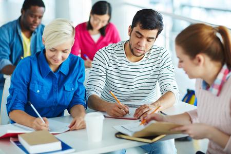 diligent: estudiantes universitarios diligentes escribir notas o asignación al hogar Foto de archivo