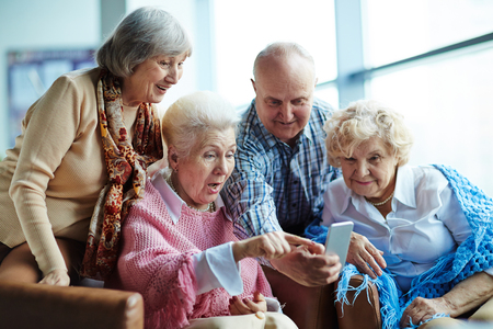 Group of surprised seniors looking at smartphone screen while sitting in cafe Imagens