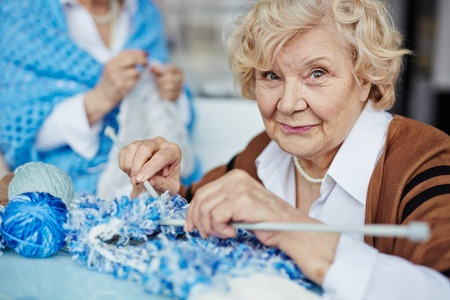 Bejaarde vrouw breien en kijken naar de camera