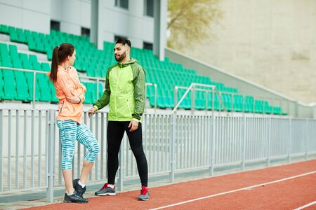 activewear: Sporty young couple in active-wear having talk at stadium