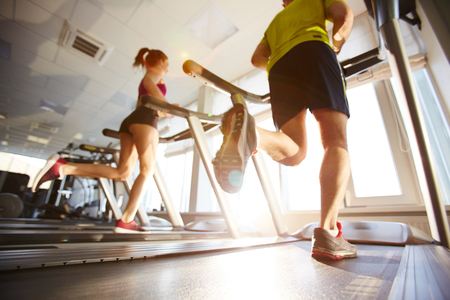 men and women: Young people running on treadmills in sport club Stock Photo