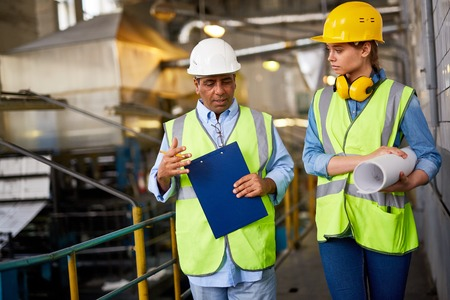 protective helmets: Two contemporary engineers in uniform and protective helmets discussing work Stock Photo