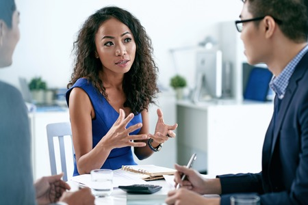 professional woman: Pretty Asian business woman explaining her idea to male colleagues