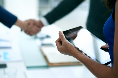 deal: Digital tablet in hands of business lady, selective focus
