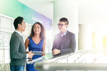 coworkers: Vietnamese coworkers having friendly talk Stock Photo