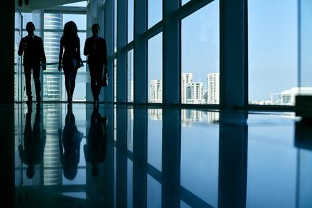 Business people walking along dark office corridor