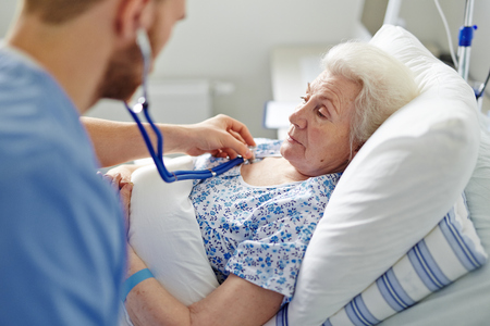 geriatrics: Male doctor examining a senioe woman in hospital ward