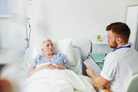 ber: Doctor sitting at ber of senior woman in hospital Stock Photo