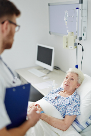 hospital patient: Male doctor consulting his senior female patient in hospital Stock Photo