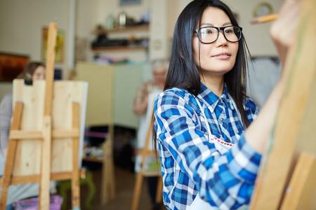 Mujer joven que aprende a pintar en clase de arte