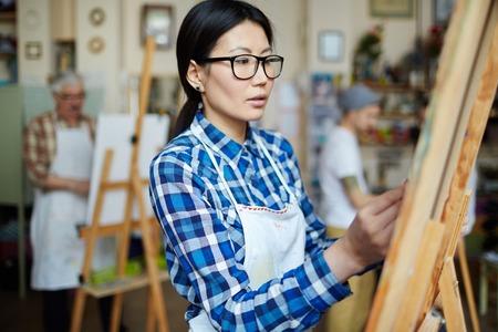 clases: Joven mujer dibujo en clase de arte del estudiante Foto de archivo