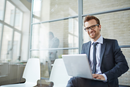 happy work: Young positive man working with laptop in office