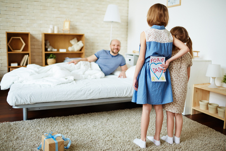 congratulating: Two sisters congratulating their father in the morning Stock Photo