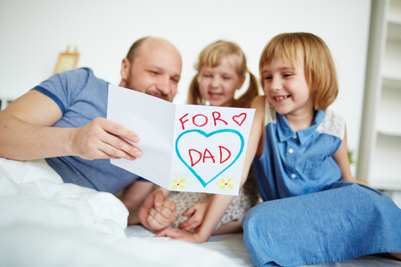 greeting card: Father reading a greeting card with his daughters