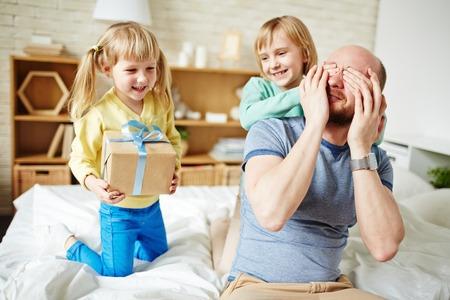 Pequeñas hijas que hace la sorpresa fot su papá en día de padres Foto de archivo