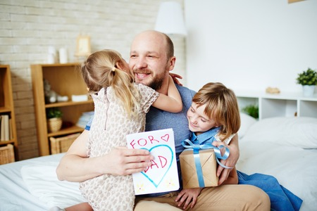 Little daughters embracing their father to congratulate with fathers day Stock Photo - 57068308