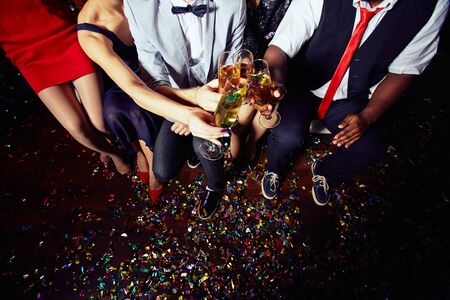 champagne flutes: Group of well-dressed people clinking champagne flutes