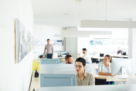 businesspeople: Woman working at computer in office with colleagues
