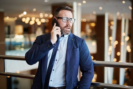 phone conversation: Mid adult businessman calling to his partner