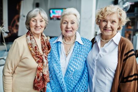 Portret van drie senior vrouwen glimlachen op camera Stockfoto