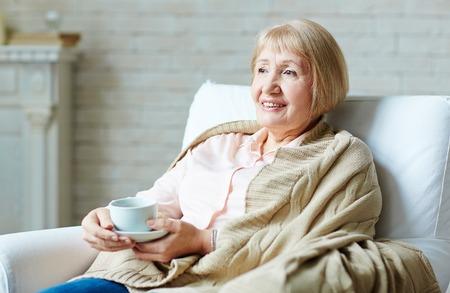 persona de la tercera edad: Mujer mayor que bebe té en casa