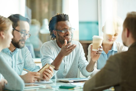 Group of workers drinking coffee and consulting