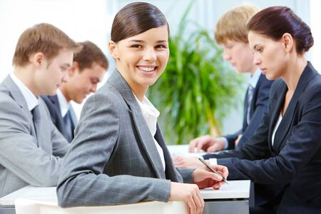 workgroup: Businesswoman sitting at table with team and smiling