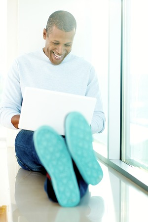 window sill: Happy man with laptop on window sill Stock Photo