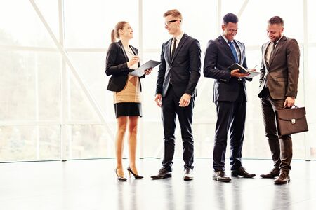 La gente de negocios de pie y hablar