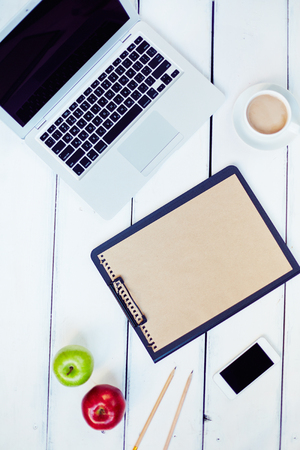 wireless telephone: Laptop, clipboard, apples, smartphone and coffee cup on wooden table