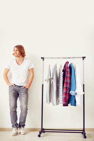 man standing: Man standing at shirt rack Stock Photo