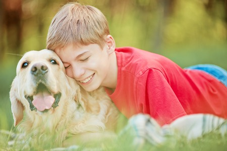 Gelukkig teenge jongen omarmen zijn hond