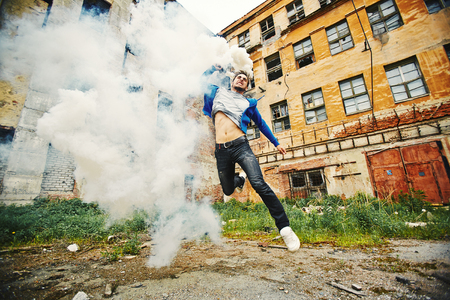 anarchist: Young man running with smoke candle in ghetto