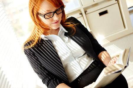 Young businesswoman reading a book photo