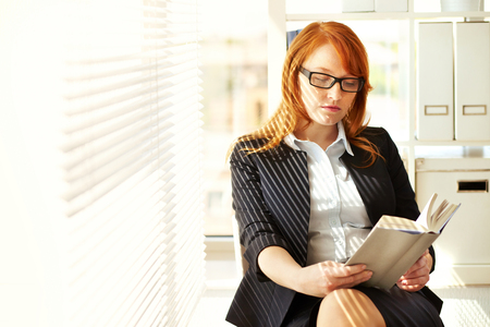 Young businesswoman resting in office with a book photo